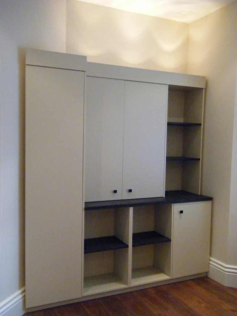 Cupboards in painted MDF shelves in black stained oak.