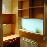 Original bathroom wall was removed and a new wall of birch ply with etched glass window to bring more light in the office.  All shelves and workstation of birch ply.